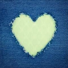 Green vintage heart on blue denim fabric