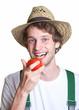 Gärtner beißt in seine Tomate