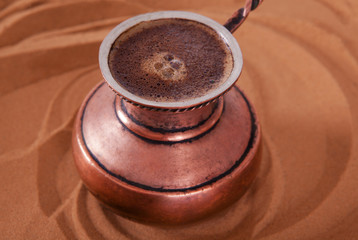 Турка с кофе на песке