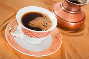 Чашка кофе  и турка  на песке