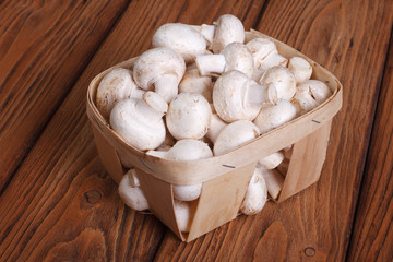 Champignon mushrooms in a basket on a wooden table. close-up