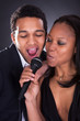 African Couple Singing With Microphone
