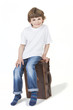Young Happy Boy Smiling Sitting on Suitcase