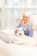 Woman with dog on the sofa holding a mug and phoning