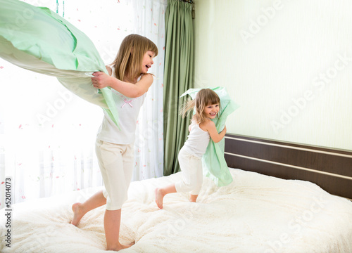 Little girls fighting using pillows in bedroom