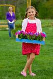 Gardening, planting - girl helping mother in the garden