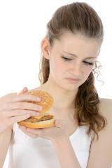 Jugendliche schaut angewidert in Cheeseburger
