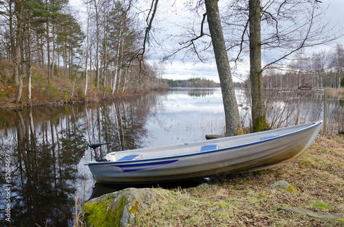 Small aluminium boat on the lake coast