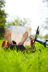 Cyclist on a halt reads a map lying on green grass in park