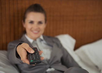Closeup on tv remote control in hand of business woman