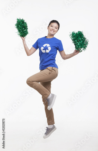 Young woman with recycling t-shirt cheering with pompoms, studio shot