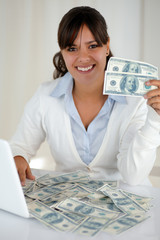 Young woman looking at you holding cash money