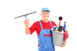 Male cleaner holding a bucket with cleaning supplies and looking