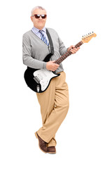 Full length portrait of a mature man with electric guitar leanin