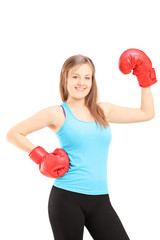 Smiling female athlete wearing red boxing gloves and posing