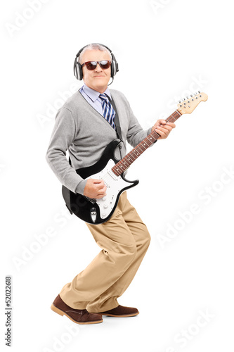 Full length portrait of a mature man with glasses playing guitar