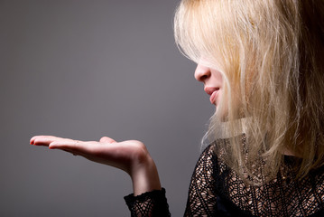 Portrait of a cute young female blowing a kiss towards copyspace