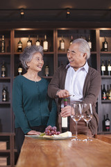 Senior Couple Opening Wine Bottle
