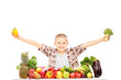 An excited kid holding broccoli, and a pepper on a table full of