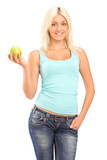 A studio shot of a blond smiling woman holding a green apple and
