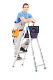 Full length portrait of a handy man posing on a ladder