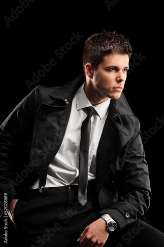 A fashionable young man with a jacket and tie posing