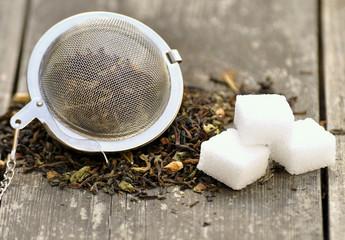 Teesieb, Teekräuter und Zuckerwürfel