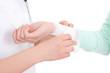 doctor bandaging female hand over white