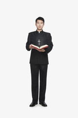 Young Priest Standing with Bible