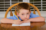 Unhappy child doing his homework at kitchen table