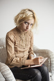 Blonde Young Woman Writing in Her Journal