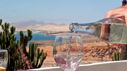 Filling a glass with water. Fuerteventura coast on background