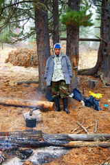 Travellier beside campfires in wood