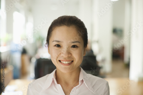 Young woman smiling in the office, portrait