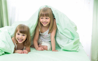 Two little girls lying under blanket on bed