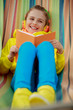 Young girl in headphones reading a book