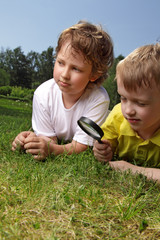 boys with magnifying glass outdoors