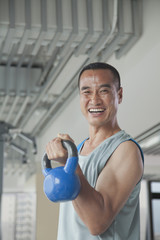 Mature man lifting weights in the gym, portrait