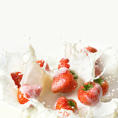 Red strawberry fruits falling into the milk