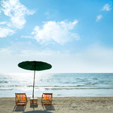 Beach chairs and umbrella on beach.