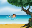 A boy swimming at the beach with an old tree