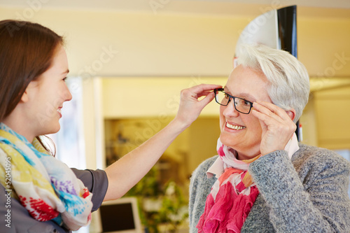 Optician advising senior woman buying glasses