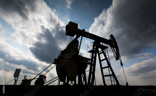 Operating oil well contour profiled on sky with clouds