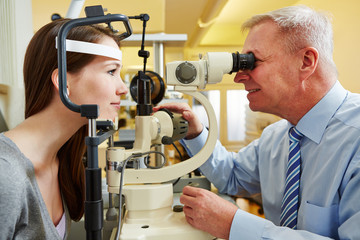 Ophthalmologist examing woman with slit lamp
