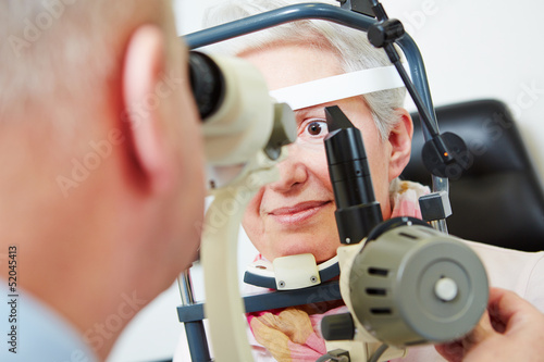 Senior woman behind slit lamp at optician