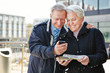 Senior couple with city guide app