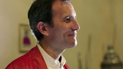 Young catholic priest on altar in church, talking and smiling