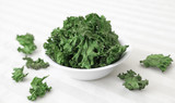 Kale Chips -  A bowl of home-made kale chips sitting on a table.