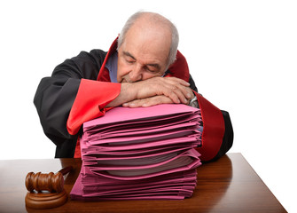 Exhausted senior adult judge sleeping on stack of law files