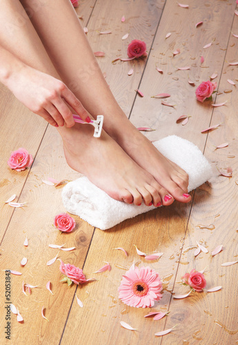 Woman shaving her beautiful legs on a spa background